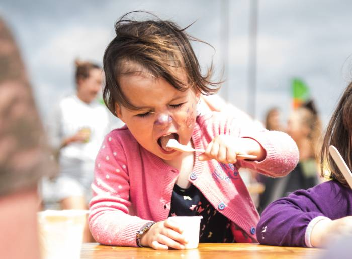 small child eating organic yogurt at festival